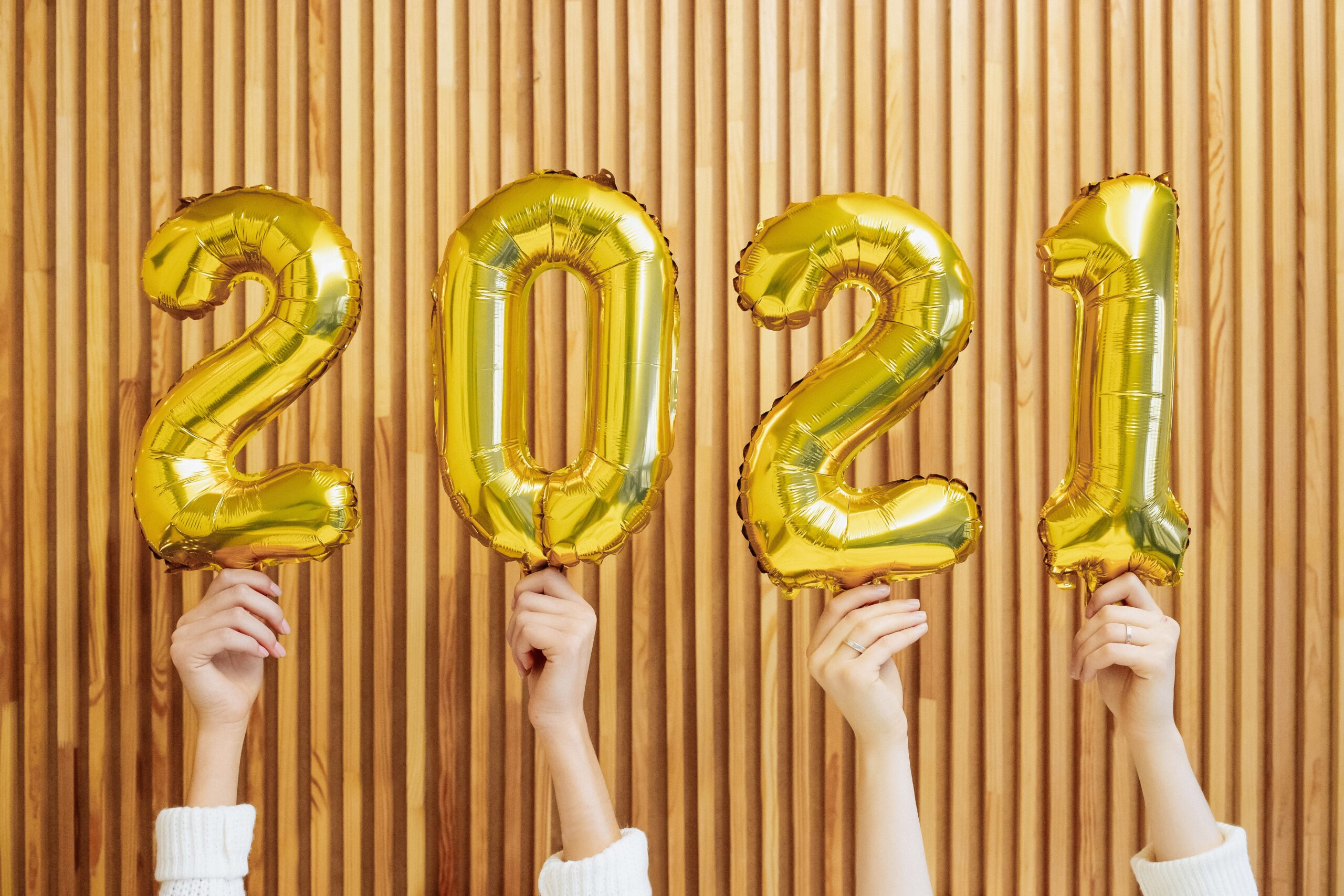 hands holding gold 2021 balloons