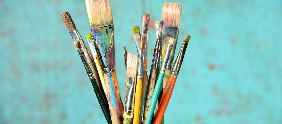 Artist paintbrushes in a jar over colorful background